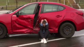 Close-up of girl sitting on the ground near a broken car, she was in an accident. A young girl sitting on the ground near his broken car, the car is destroyed by stock footage