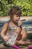 Young girl putting on lipstick. A young girl sitting on the ground and putting on lipstick Stock Photos