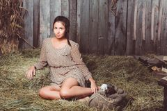 Young girl sitting on the hay with a sack stock photo