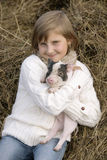 Young girl sitting on hay, smiling and holding a pig in his smiles. Lifestyle portrait Royalty Free Stock Image