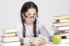 Young girl is sitting at her desk among books Royalty Free Stock Photography