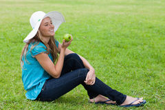 Young girl sitting while holding a green apple Royalty Free Stock Photo