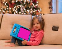 Preschool girl using a tablet computer at home at Christmas Royalty Free Stock Image