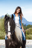 Young girl sitting on horse while crossing river. In a mountainous landscape Stock Image