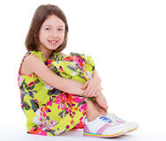 Young girl sitting hugging legs Stock Images