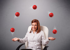 Young girl sitting and juggling with red balls. Pretty young girl sitting and juggling with red balls Royalty Free Stock Image