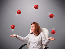 Young girl sitting and juggling with red balls Royalty Free Stock Photos