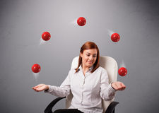 Young girl sitting and juggling with red balls Stock Images