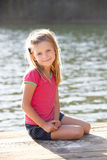 Young girl sitting by lake stock photo