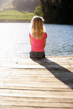 Young girl sitting by lake Stock Photos