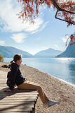 Young girl sitting on the lake shore in the autumn park. Lugano Stock Photo