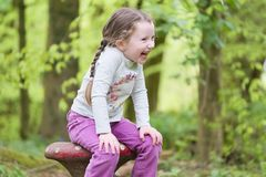 Young girl sitting laughing hands on knees in woodland forest. Uk royalty free stock photo