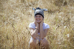 A young girl sitting in the long grass. On a beautiful summers day Stock Photos