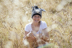 A young girl sitting in the long grass. On a beautiful summers day Royalty Free Stock Photos