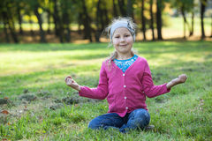 Young girl sitting in lotos pose on summer lawn Royalty Free Stock Images