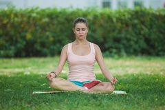 Young girl sitting in the lotus position Stock Image