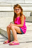 Young Girl Sitting on Marble Steps Stock Photo