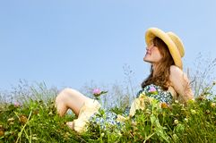 Young girl sitting in meadow Royalty Free Stock Image