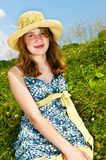 Young girl sitting in meadow Stock Photo