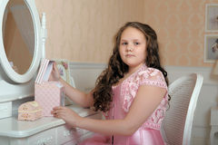 Young girl sitting at mirror in bedroom smiling Royalty Free Stock Images