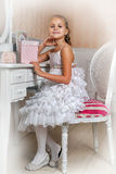 Young girl sitting at mirror in bedroom smiling Royalty Free Stock Photography
