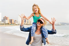 Young girl sitting on mom`s shoulder while walking on beachfront royalty free stock images