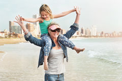 Young girl sitting on mom`s shoulder while walking on beachfront Royalty Free Stock Photo