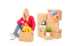 Young girl sitting with moving boxes next to her Stock Image
