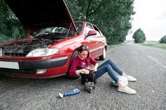 A young girl sitting near a broken car and looking for help, next to her there are bad parts, electric generator, tools and first. Aid kit royalty free stock photos