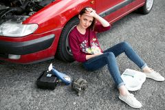 A young girl sitting near a broken car and looking for help, next to her there are bad parts, electric generator, tools and first. Aid kit stock photography