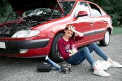 A young girl sitting near a broken car and looking for help, next to her there are bad parts, electric generator, tools and first. Aid kit royalty free stock images