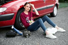 A young girl sitting near a broken car and looking for help, next to her there are bad parts, electric generator, tools and first. Aid kit royalty free stock photography