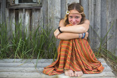 Young girl sitting near the village houses. Holidays in the village. Royalty Free Stock Images