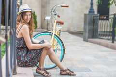 Young girl sitting near vintage bike at park Royalty Free Stock Photos