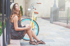 Young girl sitting near vintage bike at park Stock Photo