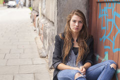 Young girl sitting near the wall on the street. Stock Image