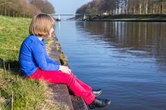 Young girl sitting near waterfront of river Royalty Free Stock Image