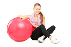 Young girl sitting next to a fitness ball Stock Photo