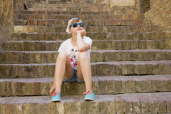 Young girl sitting on old stone stairs Royalty Free Stock Photo