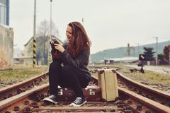 Young girl sitting on old suitcase on the track and also the old retro camera Royalty Free Stock Image