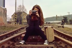 Young girl sitting on old suitcase on the track and also the old retro camera Stock Image
