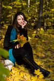 Young girl sitting outdoor in autumn scenery Royalty Free Stock Photos