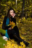 Young girl sitting outdoor in autumn scenery Stock Image
