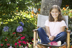 Young Girl Sitting Outdoors In Garden Chair Royalty Free Stock Images