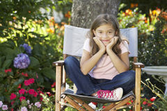 Young Girl Sitting Outdoors In Garden Chair Royalty Free Stock Photo