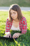 Young girl sitting outdoors on grass deals in laptop, working, pensive look, a summer day outdoors in the Park Royalty Free Stock Images