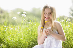 Young girl sitting outdoors holding flower smiling stock photo