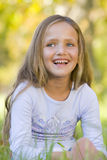 Young girl sitting outdoors smiling royalty free stock photo