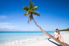 Young girl sitting on a palm tree. Saona island. Beach. Atlantic ocean coast, Dominican Republic Royalty Free Stock Image