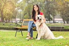 Young girl sitting in a park with her dog Royalty Free Stock Photos